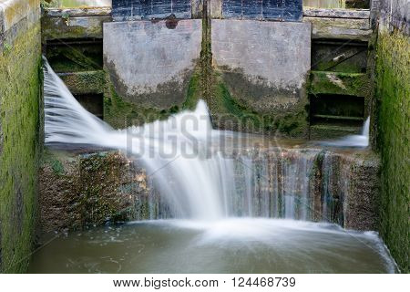 Canal lock cill with water spilling through gate. Lock with water escaping at high pressure through gaps, splashing onto cill