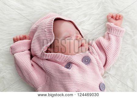 Newborn baby sleeping on white fur blanket. White background