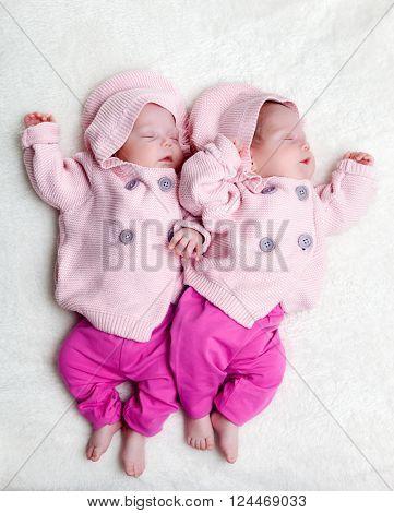 Newborn twins sisters sleeping on white fur, wearing cute pink sweaters