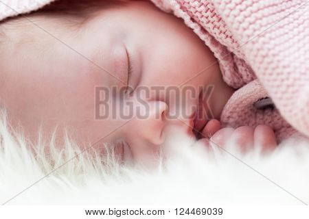 Newborn baby sleeping on white fur blanket. Close-up