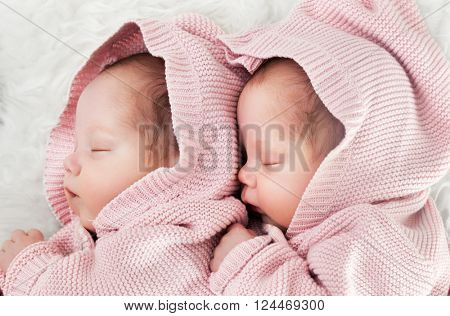 Newborn twins sisters sleeping on white fur, hugging each other and wearing cute pink sweaters