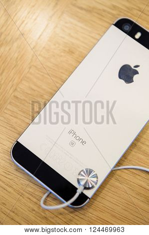 PARIS FRANCE - APR 4 2016: Rear view of the new Apple iPhone SE during the sales launch of the latest Apple Inc. smartphone and iPad Pro at the Apple store in Paris France