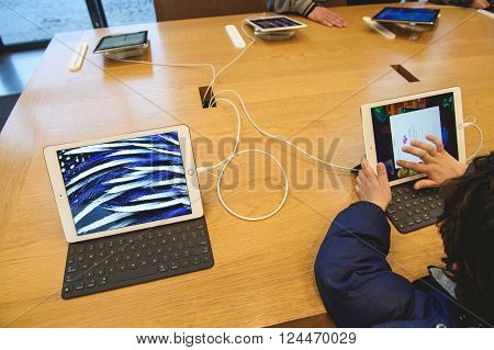 PARIS FRANCE - APR 4 2016: Kid playing game on the new 9.7-inch iPad Pro during the sales launch of the latest Apple Inc. smartphone and iPad Pro at the Apple store in Paris France