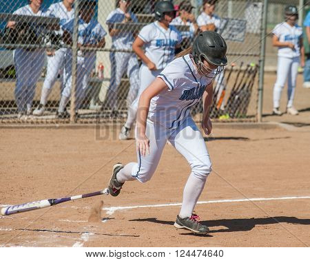 High school softball player running to first base.