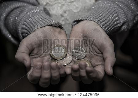 Money in the hands of a poor woman who asks for alms.
