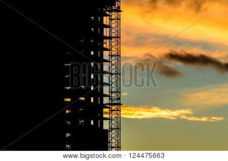 Construction site with cranes at sunset, sunrise, dawn time with the cranes as a silhouette. Vancouver, Canada.