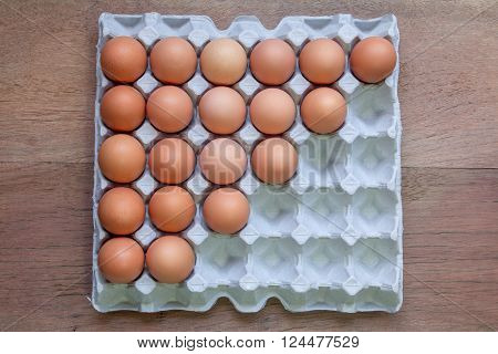 Twenty Eggs in paper tray on wooden background.