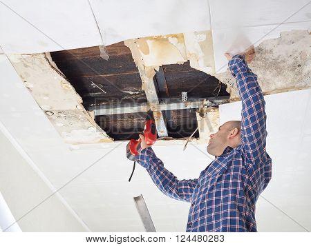Man Repairing Collapsed Ceiling