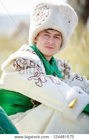 Portrait of a man on the grass in the traditional clothes looking at the camera,