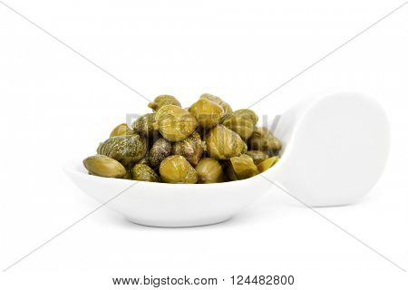 some pickled capers in a white porcelain spoon, on a white background
