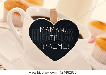 the sentence maman je t aime, I love you mom written in french in a heart-shaped blackboard placed in a cup of coffee, with some muffins in the background in a set table for breakfast