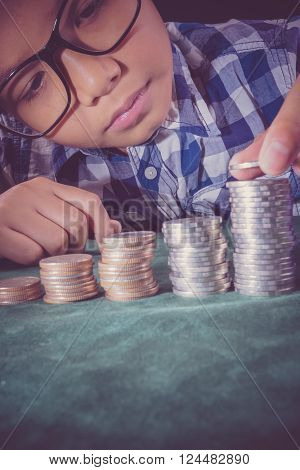 Young boy counting his saved coins and thinking about what he can buy