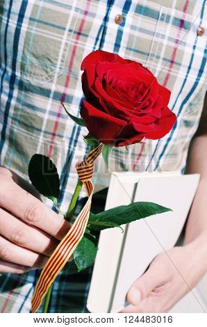 closeup of a young man with a red rose with the flag of Catalonia and a book for Sant Jordi, the Saint Georges Day, when it is tradition to give red roses and books in Catalonia, Spain