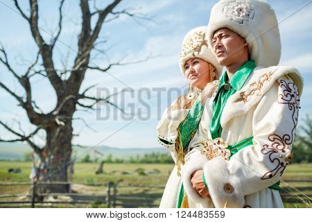 Couple in traditional dress, on a background of epic ancient tree in the middle of the rural landscape.