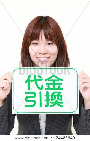 businesswoman holding a message board with the phrase CASH ON DELIVERY in KANJI