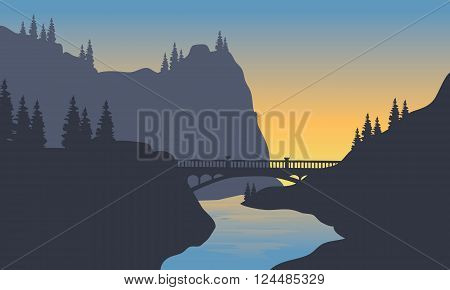 Silhouette of river and bridge at sunrise