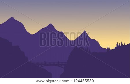 Silhouette of mountain and bridge at sunrise