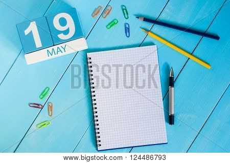 May 19th. Image of may 19 wooden color calendar on blue background.  Spring day, empty space for text.