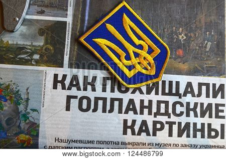 Kiev,Ukraine.FEB 20.ILLUSTRATIVE EDITORIAL.Chevron Ukrainian nazionalist battalion.Background - newspaper about West Frisian Museum stolen art . February 20,2016 in Kiev, Ukraine