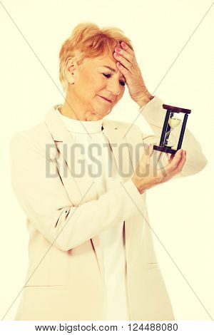 Worried elderly business woman with palm on her forehead holding hourglass