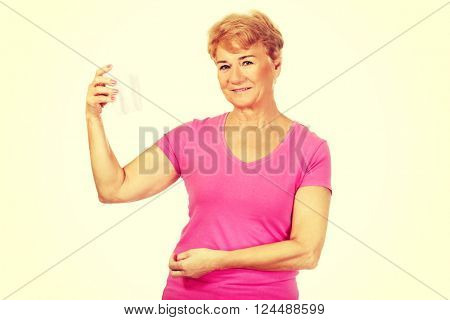Smiling senior woman holding a tooth model