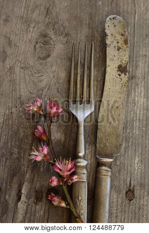 Old stylish flatware with  flowers on the table.