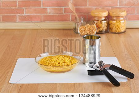 can opener and bowl of canned corn in the kitchen
