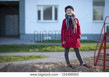 cheerful girl in red raincoat on the city playground