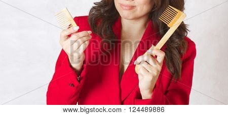 A young woman between 30 and 40 years old with a broken wooden made hair comb