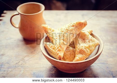 Wooden bowl of freshly baked homemade pastry with jag on an old barn wood table. Rustic background.
