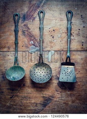 Vintage kitchen utensils on rustic wood background. Vintage utensils on scratched grunge wood surface. Vertical. Top view.