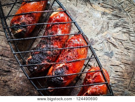 Grilling sausages in a lattice on wooden background. Barbecue grill. Fried sausages. BBQ with fiery sausages on the grill. Horizontal. Top view.