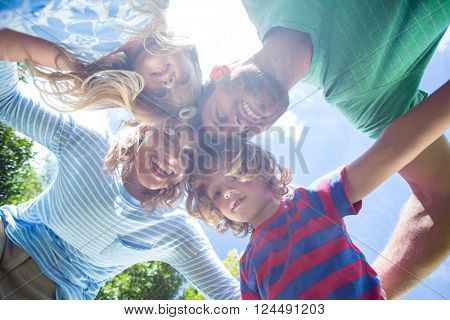 Happy parents with children forming huddle while standing at yard
