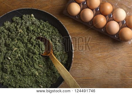 Stewed nettles with cream sauce and garlic in cooking pot with spoon on rustic background