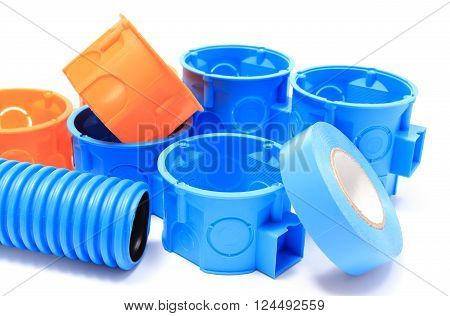 Heap of blue and orange electrical boxes with components for use in electrical installations accessories for engineering jobs