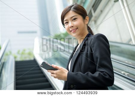 Businesswoman going up to escalator