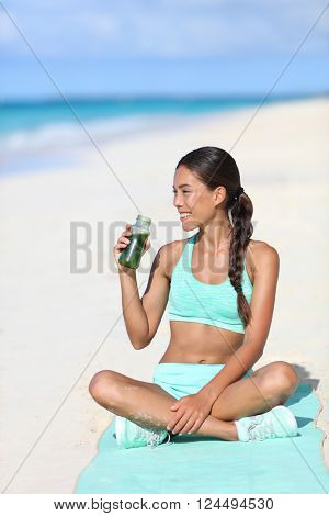 Fitness woman drinking a healthy green smoothie juice for a detox weight loss cleanse. Happy sporty asian girl  on beach taking a snack break with a vegan beverage for a vegetarian diet.