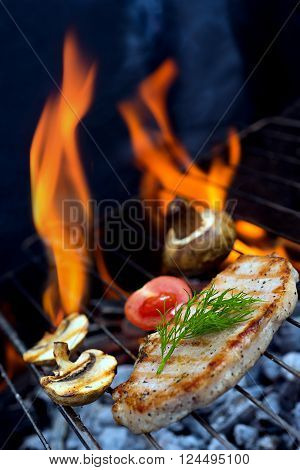 Stake grill and tomatoes with flame on background