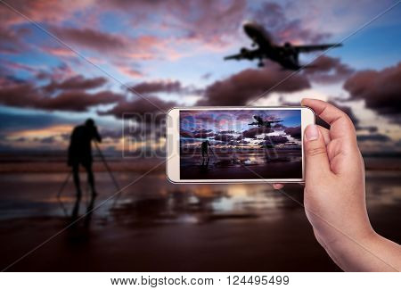 Hand of women with smart phone shooting photograph on blurred airplane and beach sunset in twilight over dark tone