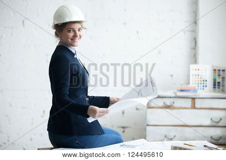 Smiling Woman In White Helmet With Blueprint