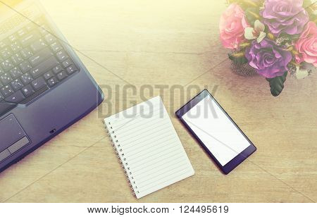 Office table with notepad Computer notebook and smartphone white screen and notepad View from above with copy space vintage style