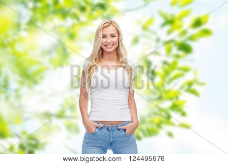 summer, advertisement and people concept - happy smiling young woman or teenage girl in white t-shirt over green natural background