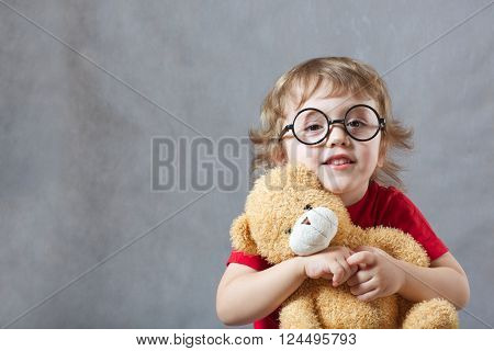 A Child With A Teddy Bear In Its Arms
