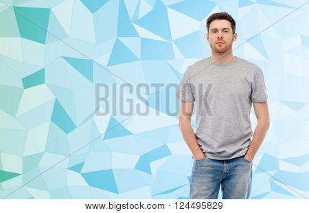 male, gender, fashion and people concept - young man in gray t-shirt and jeans over blue low poly texture background
