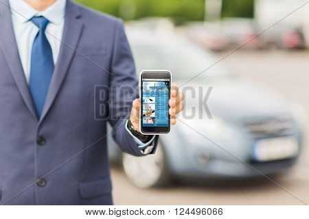 transport, business trip, mass media, technology and people concept - close up of man showing internet news page smartphone screen on car parking
