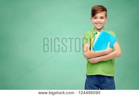 childhood, education and people concept - happy smiling student boy with folders and notebooks over green school chalk board background