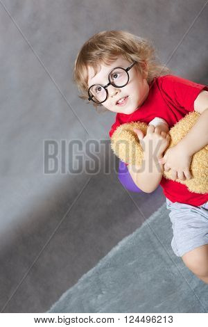 A funny child of 3 years old with long hair hugs a brown plush teddy bear on a gray background Free space for a text.
