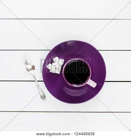 cup of tea or coffee on violet plate silver tea spoon lump sugar on white colored wooden table top view