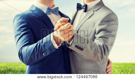 people, homosexuality, same-sex marriage and love concept - close up of happy male gay couple holding hands and dancing over blue sky and grass background