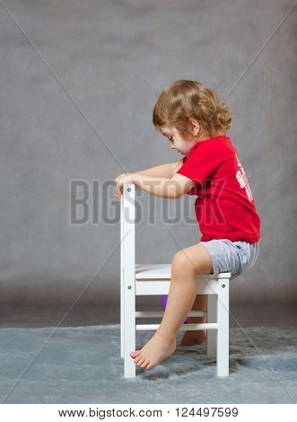 A Boy And A White Chair. Gray Background